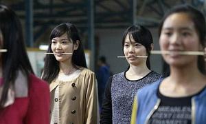 Thiếu nữ Trung Quốc ngậm đũa để học cười
