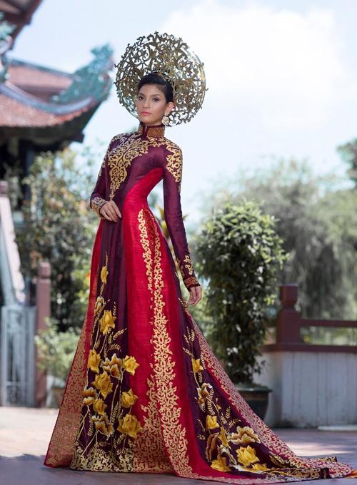 Các họa tiết ở tà áo dài được thêu tay tỉ mỉ và ép nhũ vàng. Chất liệu chính của trang phục là lụa truyền thống đính pha lê, với hai màu chủ đạo là vàng đồng và đỏ sậm. Nhà thiết kế lấy ý tưởng hoa sen để thiết kế, tượng trưng sự tinh khiết, dịu dàng.