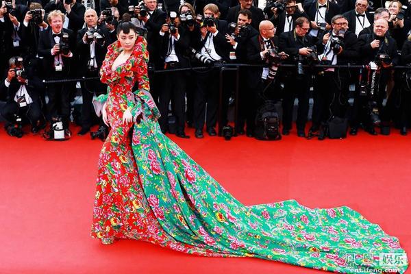 """Lần đầu tiên được đến tham dự LHP Cannes lần thứ 68, Trương Hinh Dư lập tức trở thành tâm điểm với bộ váy lấy cảm hứng từ chiếc chăn con công """"huyền thoại"""". Chiếc váy xanh đỏ khiến Hinh Dư bị ví như đang trải chăn trên thảm đỏ Cannes."""