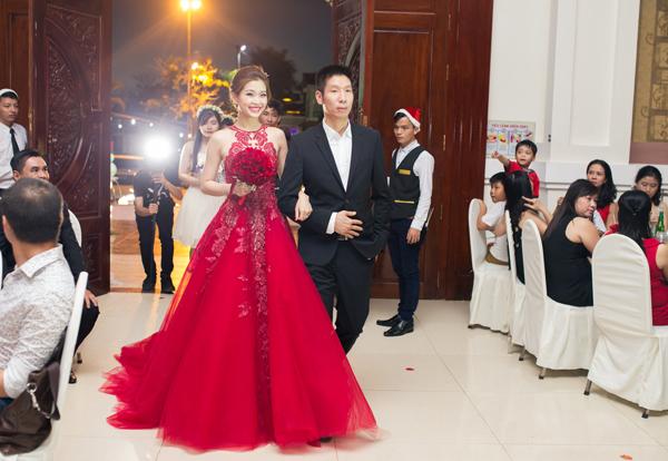 Hôn lễ được tổ chức sát ngày Noel nên không gian cưới ngập tràn không khí giáng sinh. Á hậu sinh năm 1991 thay váy cưới xuyên thấu màu đỏ của Luciola Nguyễn.