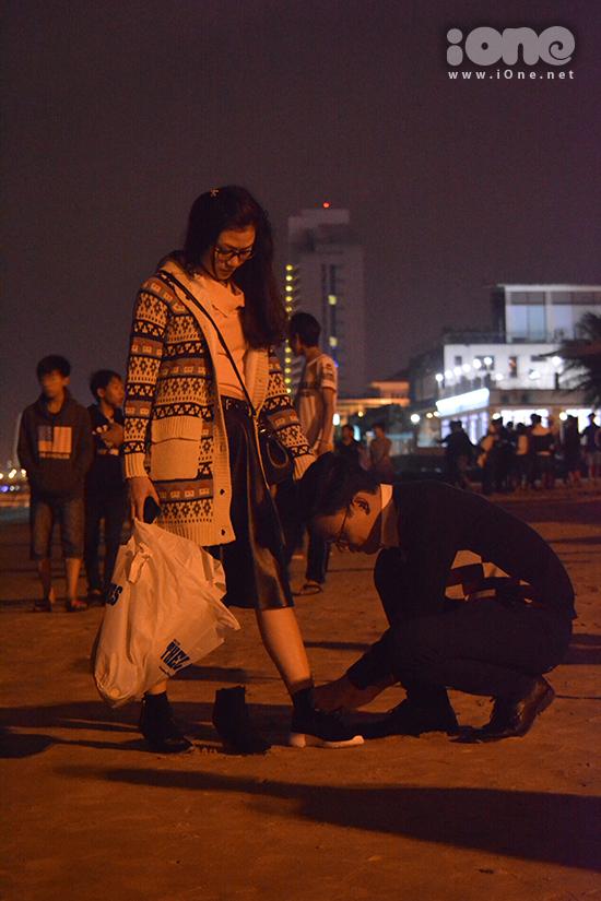 Nhiều cặp đôi hẹn hò trong không khí lãng mạn chào năm mới. Một anh chàng cúi xuống buộc lại dây giày bị tuột của bạn gái vì chen chúc trong đám đông.