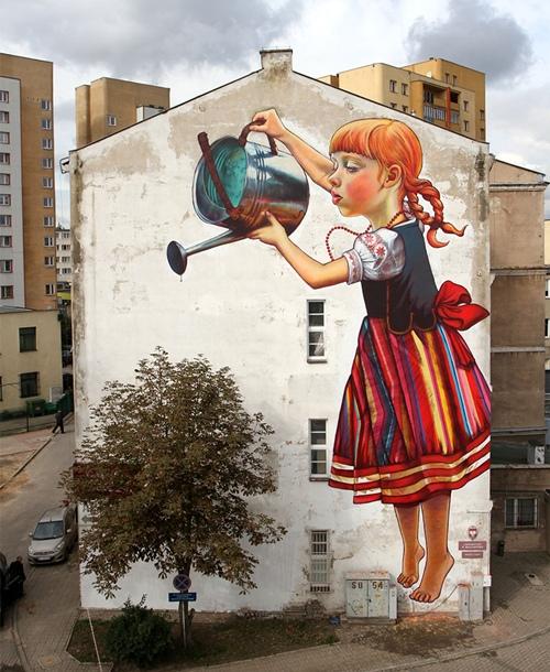 Một bức tranh cô bé tưới cây được vẽ trên tòa nhà thay cho lời thông điệp bảo vệ cây xanh.