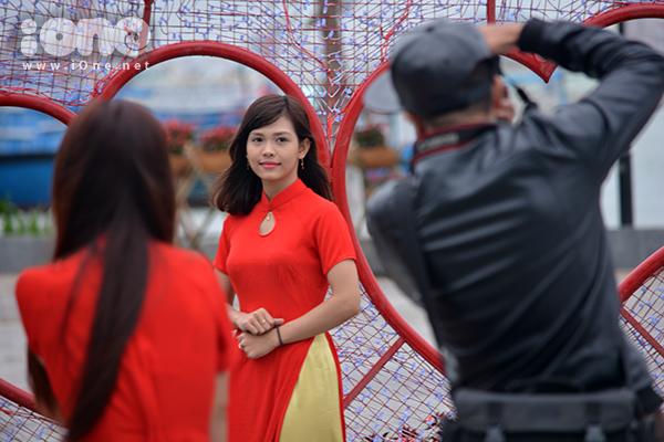 Màu áo dài đỏ của một bạn gái hòa sắc bên những sắp đặt tình yêu ở đường hoa cạnh cầu Rồng.