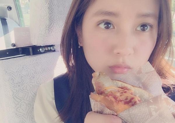 Kana tranh thủ ăn trưa trong xe taxi.