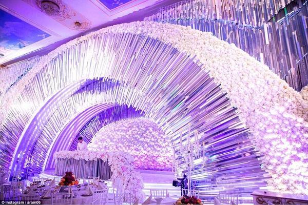 Dàn đèn chùm và hoa tươi được trang trí rực rỡ, thiết kế hoành tráng trong phòng tiệc cưới.