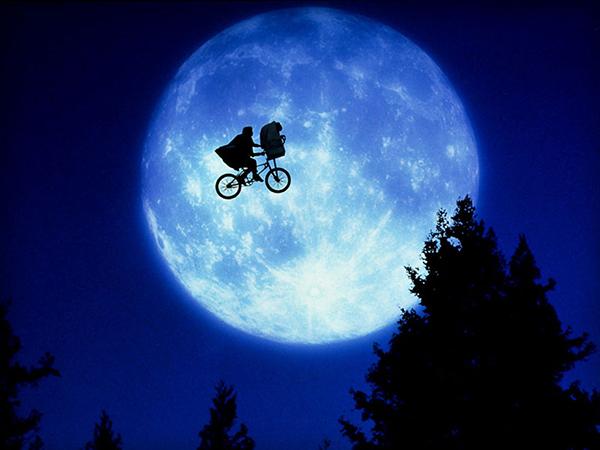 et the extra terrestrialElliott chở ET trên chiếc giỏ xe đạp trong ánh sáng xanh huyền bí.