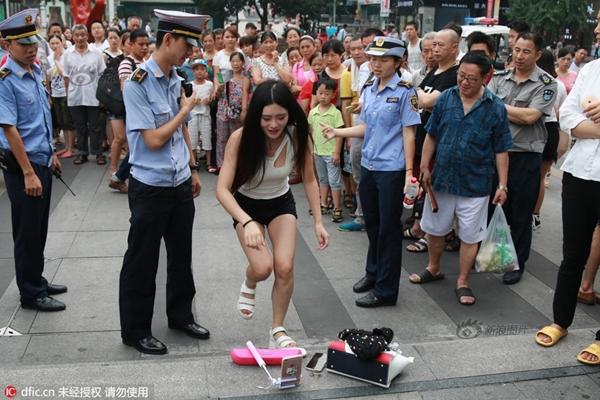 Sau một hồi gây náo động, đội trật tự đô thị xuất hiện yêu cầu cô gái rời đi vì làm ảnh hưởng đến an ninh trật tự.