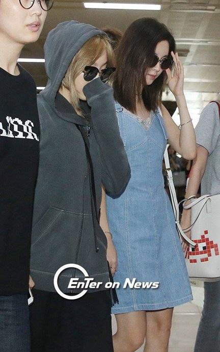 Tae Yeon mặc áo hoodie, trùm mũ, che kín gương mặt.