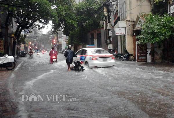 Nước ngập khiến một số người dân đi xe máy phải dắt bộ vì ngập sâu. Trong ảnh là   phố Tô Vĩnh Diện, quận Thanh Xuân.