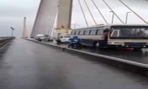 Ô tô đi chậm che cho xe máy qua cầu trong cơn bão