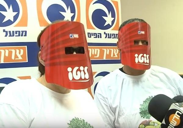 Cặp đôi người Israel mặc trang phục đặc biệt và đeo mặt nạ để che giấu danh tính trước truyền thông sau khi trúng số.