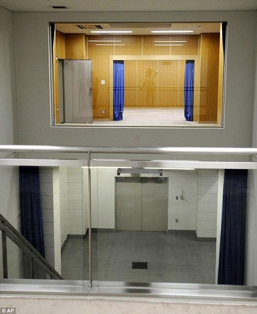 Tử tù được đưa vào căn phòng ốp gỗ có rèm xanh phía trên, bị buộc dây thừng   quanh cổ rồi bị thả xuống căn phòng lát gạch xám bên dưới.