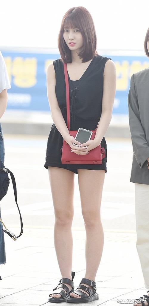 Cô nàng khoe dáng khỏe khoắn với bộ jumpsuit ngắn, xăng đan và túi đỏ đeo chéo tạo điểm nhấn.