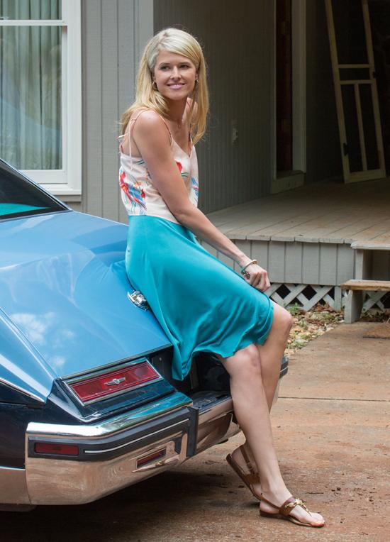 Cô vợ xinh đẹp Lucy của Barry Seal (do nữ diễn viên Sarah Wright thủ vai) bên chiếc xế cổ màu xanh đậm cổ điển trong phim.