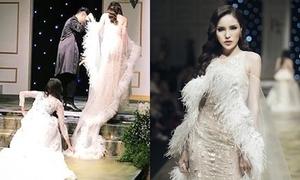 Lan Khuê cúi người nâng váy cho Kỳ Duyên trên sàn catwalk