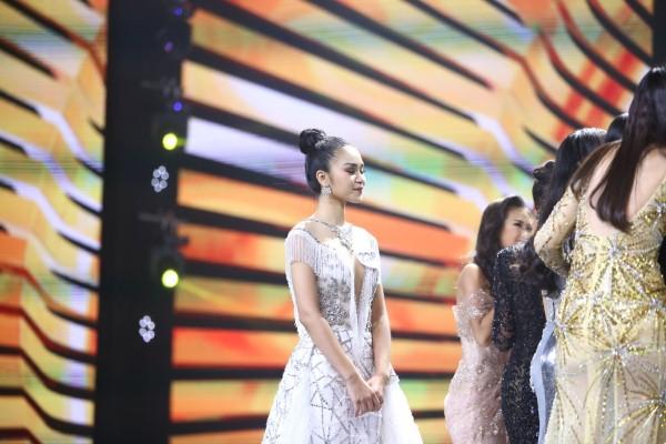 Lê Thu Trang đứng riêng một góc khi các thí sinh tiến tới chúc mừng tân hoa hậu.