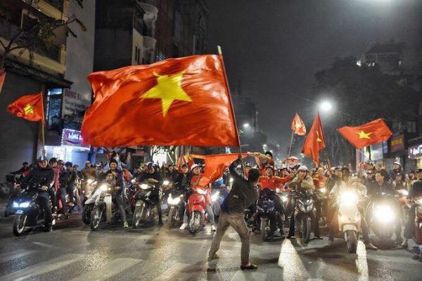 Dòng người ra đường ăn mừng với cờ Tổ quốc trên tay.