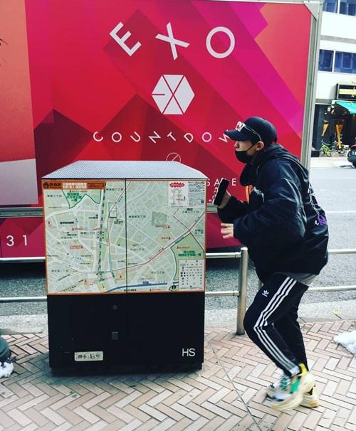 Chan Yeol (EXO) tí tởn tạo dáng khi thấy xe buýt quảng bá album mới của nhóm chạy trên đường phố Shibuya.