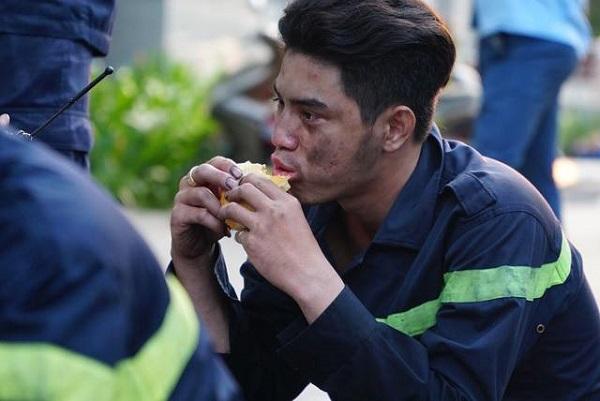 Một anh lính cứu hỏa để mặc khuôn mặt đen nhẻm vì khói bụi, ngồi ăn bánh mì lấy lại sức sau vụ cháy.
