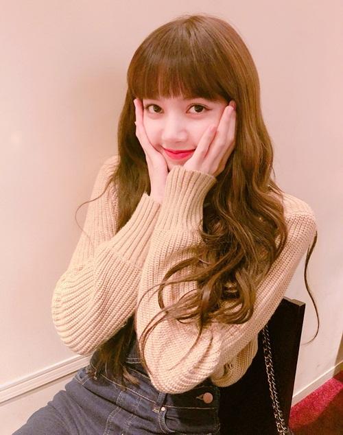 Lisa (Black Pink) ôm má đáng yêu khi cảm ơn fan đã gửi quà, chúc mừng sinh nhật cô nàng. Thành viên người Thái Lan được khen xinh như búp bê với mái tóc dài gợn sóng, mái bằng.