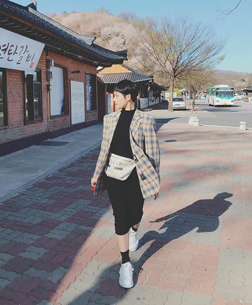 Miu Lê chọn style năng động khi đi du lịch ở Hàn Quốc. Váy thun, blazer kẻ sọc và túi đeo ngang hông cho cô nàng vẻ ngoài rất trẻ trung.