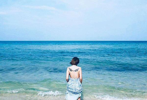 Vân Hugo diện váy maxi hở lưng trần, lộ hình xăm cánh thiên thần khổng lồ trên bả vai.