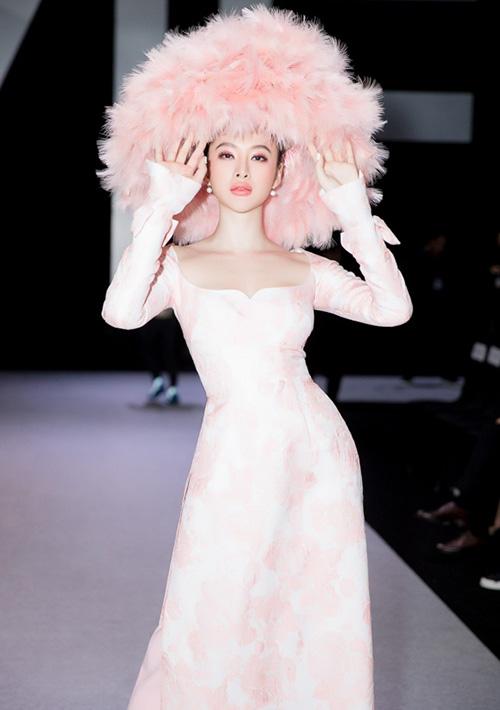 Vì trang phục lấy cảm hứng từ tà áo dài nên Phương Trinh diện cùng nón lá. Tuy nhiên chiếc nón truyền thống đã được biến tấu hiện đại bằng cách đính kết lông vũ hồng tông xuyệt tông, tạo nên tổng thể vừa hoài cổ vừa mới mẻ.