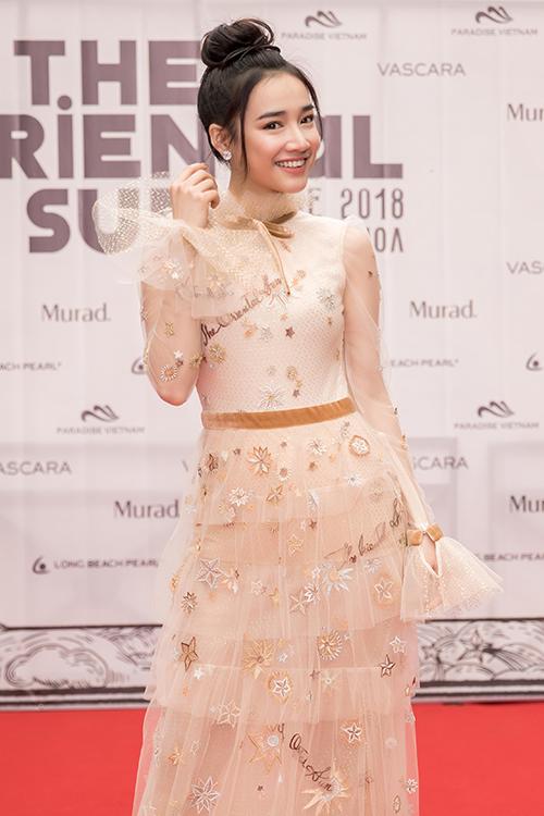 Nữ diễn viên búi tóc cao, chọn mặc một thiết kếmàu nude đầy thanh lịch mà vẫn cuốn hút. Cô rất vui vẻ, rạng ngời khi chụp ảnh thảm đỏ.