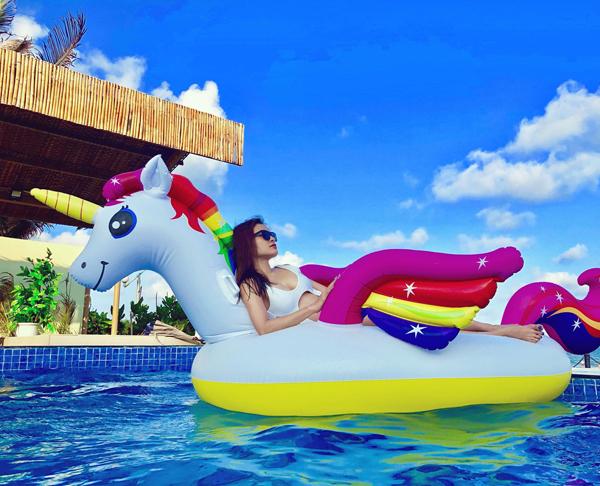 Phương Trinh Jolie nằm phơi nắng trên chiếc phao hình ngựa một sừng khổng lồ, giữa khung cảnh trời xanhmây trắng như cổ tích.