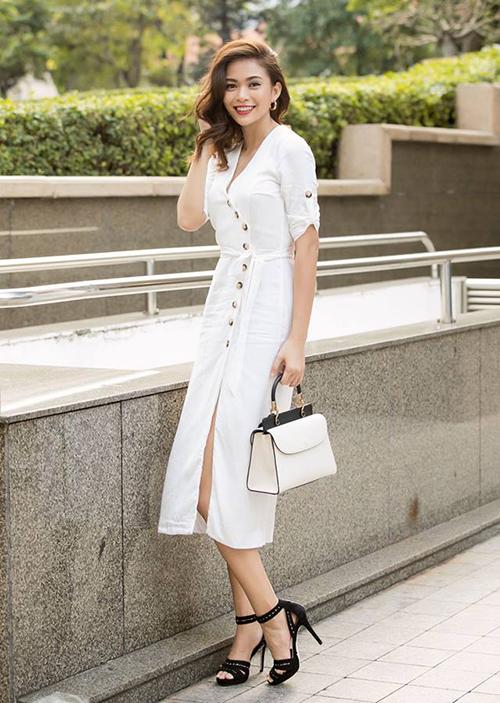 Mâu Thủy tỏa nắng trên phố trong chiếc váy trắng đính khuy, kết hợp phụ kiện đen trắng ăn ý.