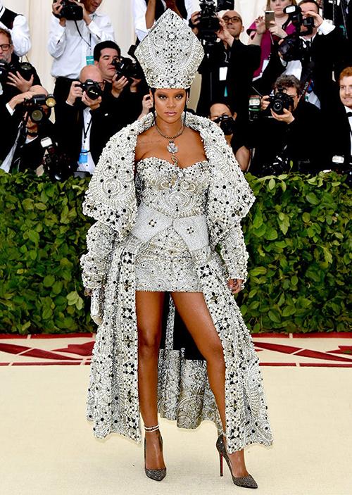 Khác với vẻ giản dị bất ngờ của chị em nhà Kim, các ngôi sao khác đồng loạt trưng diện những trang phục cầu kỳ. Rihanna tiếp tục là tâm điểm của thảm đỏ Met Gala với bộ đồ áo choàng, váy ngắn mô phỏng hình ảnh của Giáo hoàng.