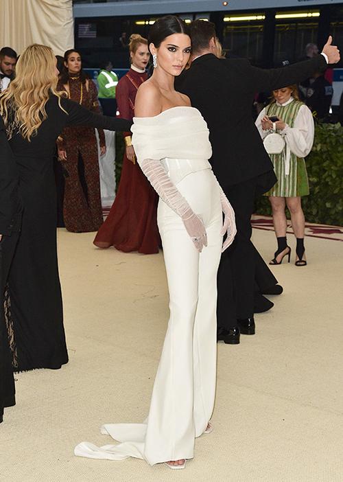 Cô em Kendall Jenner cũng không chơi trội với đồ sexy như mọi năm. Chân dài diện cây trắng với áo trễ vai, quần ống loe khá thanh lịch.