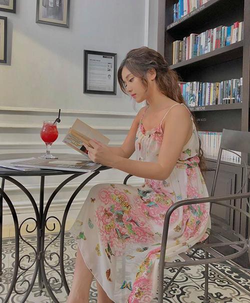 Hoàng Yến Chibi diện váy bánh bèo ngồi làm dáng đọc sách.