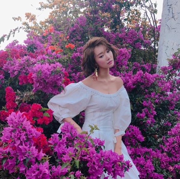 Go Joon Hee nổi bật trên nền hoa, khoe vai trần với xương quai xanh gợi cảm trong một shoot hình.