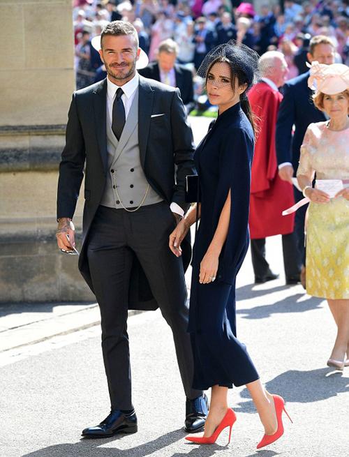 Thể hiện đẳng cấp của những người sành thời trang, Vic - Beck chọn trang phục tông xuyệt tông gam màu xanh tím than. Đây là một trong những gam màu truyền thống của hoàng gia. Trong khi Vic diện váy đến gần mắt cá chân, kết hợp giày cao gót màu nổi thì Beck lại mặc vest đuôi tôm lịch lãm.
