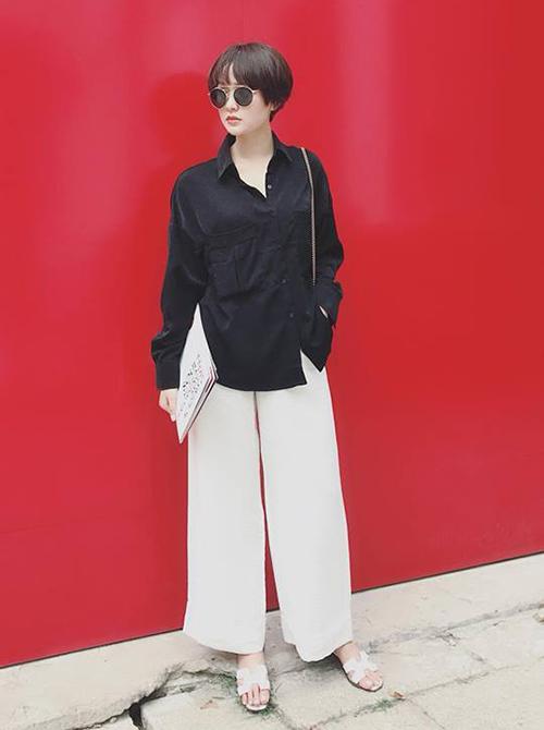 Hiền Hồ diện sơ mi đen với quần ống suông kín cổng cao tường, tuy nhiên trông vẫn rất hợp với không khí mùa hè nhờ đôi dép lê và kính mắt tròn sành điệu.