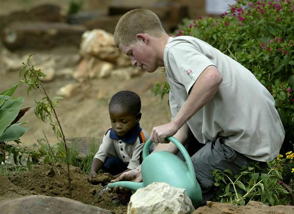 Hoàng tử Harry trồng cây ăn quả với cậu bé 4 tuổi Mutsu tại trại trẻ mồ côi năm 2004Ảnh: Reuters