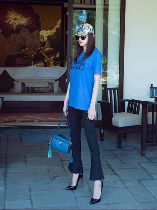 Áo phông và mũ lưỡi trai được Hương Giang thổi vẻ sang chảnh bằng quần ống loe và giày cao gót.