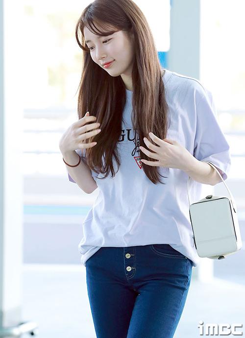 Suzy rạng rỡ ra sân bay bất chấp việc đang bị kiện bởi một studio. Nữ ca sĩ mặc áo phông của thương hiệu mà mình làm người mẫu đại diện. Mỹ nhân nhà JYP tỏa sáng với cách trang điểm nhạt.