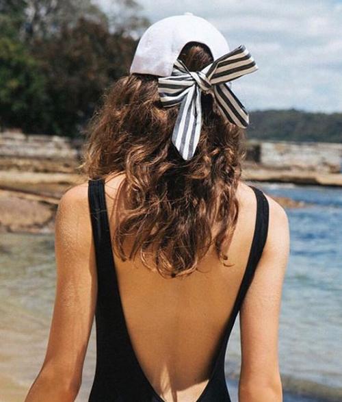 Vẫn là dáng mũ lưỡi trai vành oval quen thuộc, nhưng ở phía sau, phần khóa kim loại cứng nhắc được thay bằng vải thắt nơ, giúp chiếc mũ trở nên điệu đà hơn hẳn.