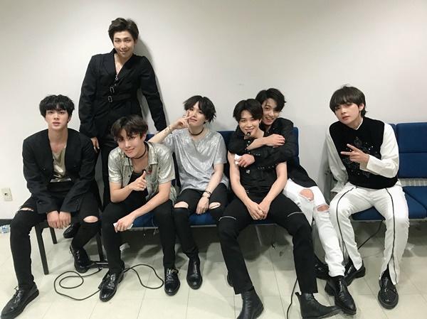 Các thành viên BTS hớn hở chụp hình trong hậu trường show âm nhạc.