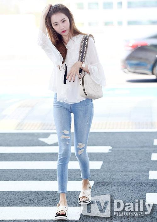 Sun Mi ra sân bay cũng thần tahsi không kém cạnh khi bước lên sân khấu. Quần skinny jean giúp nữ ca sĩ khoe đôi chân thon, vòng hông gợi cảm. Xăng đan là phụ kiện được ưa chuộng thay cho những đôi giày bức bối khi vào hè.