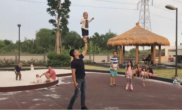 Bé tỏ ra thích thú khi đứng trên tay bố ở trên cao.