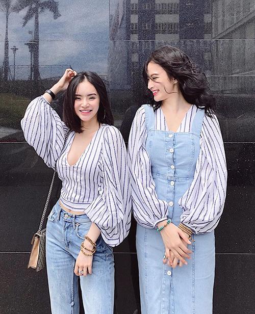 Hai chị em Angela Phương Trinh so tài mix đồ với cùng một item là áo sơ mi tay bồng và chất liệu denim. Trong khi Phương Trang gọn gàng với quần jeans thì cô chị lại nhí nhảnh hơn hẳn khi mix với váy yếm.
