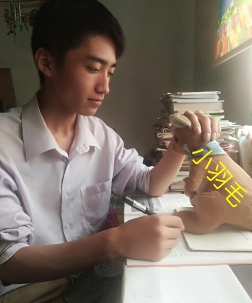 Trương Vạn Bằng mặc áo sơ mi trắng giản dị ngồi bên bàn học.
