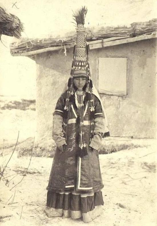 Cô gái người Kazakh đang đội một chiếc mũ sắt hình chóp lạ mắt khá to và dài.