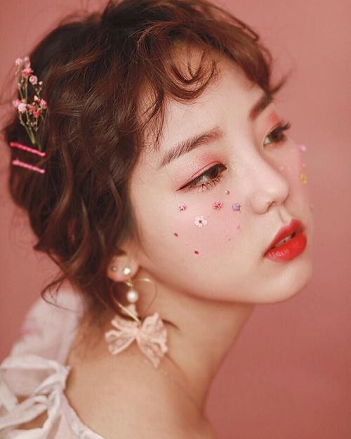 Mốt đính những cánh hoa li ti cũng được con gái Hàn áp dụng thường xuyên vì tăng độ trẻ trung, đáng yêu cho gương mặt, đặc biệt rất thích hợp với lối trang điểm da trong veo, má hồng đậm, môi đỏ mà phái đẹp xứ kim chi theo đuổi.