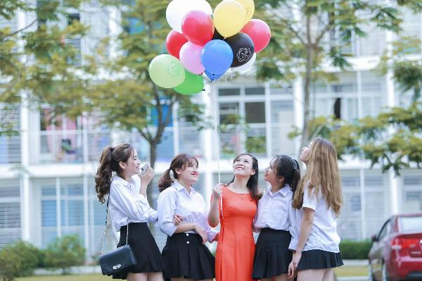 Nữ giáo viên trẻ chụp ảnh cùng học sinh.