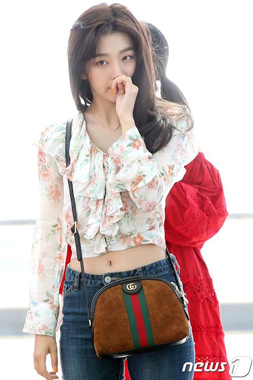 Seul Gi luôn là thành viên sở hữu mái tóc bay bổng khi ra sân bay. Cô nàng khoe eo thon với mẫu áo sơ mi bèo nhún, tạo điểm nhấn với túi Gucci đắt giá.