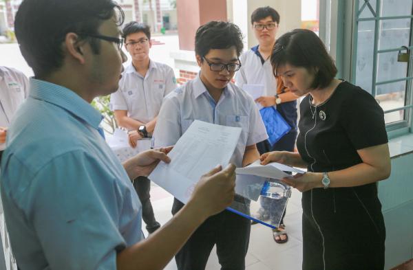 Các thí sinh đang đối chiếu lại thông tin trên thẻ dự thi một lần nữa. (Ảnh: Quỳnh Trân)
